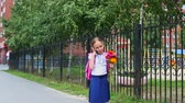 halenka : Young girl standing near school talking by cell phone and go away. Back to school concept. Summer day outdors handheld shot. Pretty elementary girl speaking by phone standing with backpack and flowers
