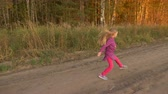 малиновый : Young white girl twisting and turning. Girl jumping by country road at sunset evening. Golden autumn