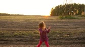 clap : Young white girl clapping by hands at sunset rural scene. Beautiful girl dancing and looking around.