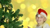 köknar ağacı : Happy young girl dancing near christmas tree in Santa red hat. Happy young caucasian girl indoors studio close up shot. Golden background. Decorated christmas tree.