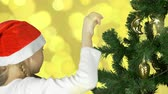 köknar ağacı : Young caucasian girl in red Santa hat decorate green christmas tree with golden sphere ball. Prepairing to celebrate Merry Christmas and Happy New Year. Abstract gold flickering lights background.