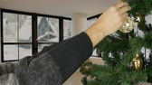 köknar ağacı : Mans hand decorate christmas tree. Country home background. Green Christmas tree. Christmas decorate. Outside the window is a snowstorm, snowfall and countryside. Snowing winter weather. Stok Video