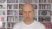 dissatisfied : Portrait angry man face looking into camera on bookcase background
