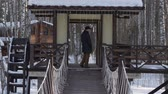 wintertime : Man going on the bridge and standing on wooden building
