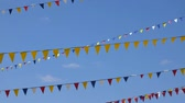 karnawał : Yellow, blue, white and red triangle flags for carnival party on sky background. Seamless loop background.