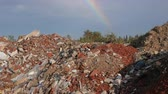 unclean : Spilled garbage and colorful rainbow at blue sky. Environmental pollution. Ecological problem. Concept ecology