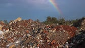 reutilização : Pollution concept with garbage dump and beautiful rainbow in blue sky