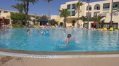 tunisia : Monastir, Tunisia - 05 June 2018: funny girl teenager diving in deep swimming pool in hotel. Happy girl jumping in water floating pool at resort hotel. Slow motion.