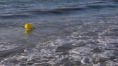 tied up : Yellow buoy floating on shallow in sea with waves, 120fps slow motion concept Stock Footage