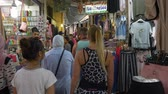 выбор : Tunis, Tunisia - 06 June 2018: tourist people walking arabian souk and looking souvenirs and gifts in old Medina city. Arab sellersworking on traditional bazaar. Стоковые видеозаписи