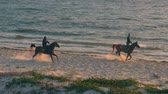 tunisia : Monastir, Tunisia - 08 June 2018: two riders on horse riding at sandy beach on sea background. Rider galloping on horses on sea shore while morning sunrise.