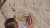 eğlenmek : Blonde kid pouring water and making cake from sand on beach, overhead view