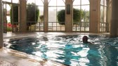 kel : Man swimming in fresh water with flares and resting in indoor pool