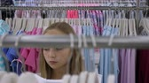 butik : Blonde girl fitting clothes on hangers and shopping in boutique
