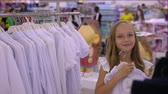 tentação : Adorable smiling girl trying and fitting white blouse in boutique Stock Footage