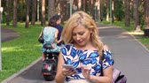 cihaz : Happy woman using mobile phone while walking in summer park