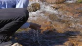 bottom view : Man drinking spring water from hand in mountain. Drinking spring in mountains