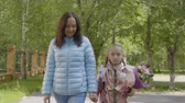 uczeń : Mom and schoolgirl holding hands and going back to school