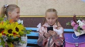 backtoschool : Two happy schoolgirls with phone and flower bouquets sitting on bench Stock Footage