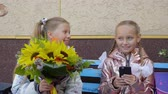 backtoschool : Two young schoolgirls with phone and bouquet going back to school