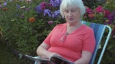 ev hayatı : Senior woman reading magazine in garden with flowers outdoor