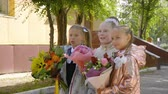 backtoschool : Three school girls with flowers posing for camera. Back to school concept