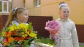 teach : Portraits pupil girls with bouquet flowers, back to school concept Stock Footage