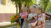 backtoschool : Cheerful schoolgirls with flowers talking and standing near school together Stock Footage