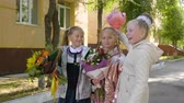 backtoschool : Playful schoolgirls with bouquets laughing and standing near school