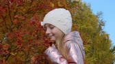 urlop : Portrait young girl on background red and orange autumn foliage on tree in park Wideo