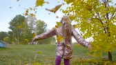 ayrılmak : Happy teenager girl toss up yellow leaves in autumn park slow motion Stok Video