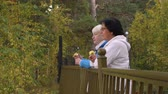 metade do comprimento : Active seniors eating apples and standing near fence in autumn park