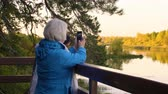 metade do comprimento : Two senior women photographing river on phone in autumn park Stock Footage