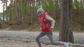 mít : Cheerful young girl dancing in forest outdoors in slow motion