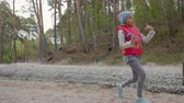 eğlenmek : Adorable preteen girl in hat and warm vest dancing outdoors