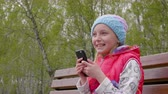 mobility : Cheerful young girl talking and using phone on bench in park