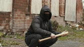 vandal : Bandit man in black mask and jacket with hood with baseball bat sits on street