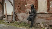 vandal : Hooligan in black mask and hood with baseball bat leaning back on brick wall