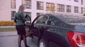kierownica : Business woman sitting into car on parking lot. Auto lady, woman driver concept Wideo