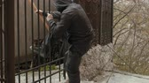 sopa : Robber in mask holding bat and sliping through the fence
