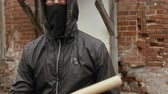 vandal : Angry hooligan in black mask and hood making kick to camera