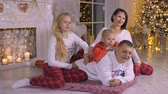 брюки : Happy family mom dad, daughter red pants and son lying on carpet on Christmas tree and fireplace background in cozy home. Happy family in cozy home at Christmas eve. Happy New Year concept