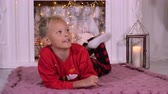 making a wish : Young blonde boy lye at floor on christmass fireplace background interior. Red pullover. Caucasian white young boy. Xmass lantern