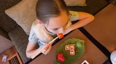 pauzinho : Teenager girl eating red japanese sushi roll with chopsticks in asian restaurant top view. Girl teenager eating traditional sushi roll in japanese cafe. Asian cuisine, food and snack concept overhead