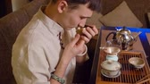 tea brewing : Tea master potter sniffing leaves in chahai before chinese tea ceremony preparation. Traditional tea ceremony. Original method and equipment for preparation tea. Close up profile view Stock Footage