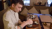 koflík na čaj : Tea master using hot water for warming bowl chahai and fairness pitcher while tea ceremony. Man preparing using original equipment for preparation traditional chinese tea at tea boat