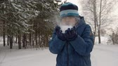 śnieżka : Young boy teenager holding in hands snow in winter forest. Boy teenager blowing and throwing up snow while winter walk in snowy forest. Winter activity concept. Guy fall down Wideo