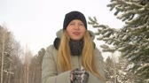 hófúvás : Young blond girl holding in hands snow. Girl blowing and throwing up snow in winter forest. Winter leisure and activity. Teenager girl in snowy forest at winter vacation Stock mozgókép