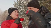 tea time : Happy couple drinking hot tea while winter walk in snowy forest close up. Portrait Man and woman in love drinking tea while romantic date in winter park. Winter tea drinking Stock Footage
