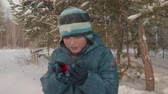 warme thee : Boy drinking hot tea. Cute teenager drinking hot tea from the red teacup during his hiking walk in the winter forest. Slow motion